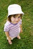 Muchacha linda que presenta en la hierba verde Imagen de archivo