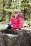 Muchacha linda que presenta mientras que descansa en una roca imagenes de archivo
