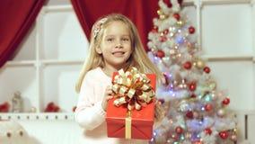 Muchacha linda que salta de la felicidad que consigue un regalo por el Año Nuevo Foto de archivo libre de regalías