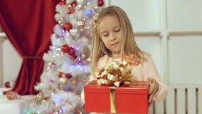 Muchacha linda que salta de la felicidad que consigue un regalo por el Año Nuevo Foto de archivo