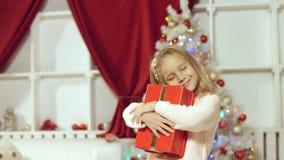 Muchacha linda que salta de la felicidad que consigue un regalo por el Año Nuevo Imagen de archivo libre de regalías