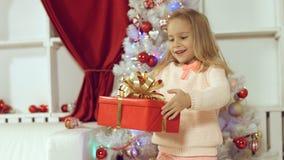 Muchacha linda que salta de la felicidad que consigue un regalo por el Año Nuevo Fotos de archivo libres de regalías