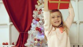 Muchacha linda que salta de la felicidad que consigue un regalo por el Año Nuevo Imágenes de archivo libres de regalías