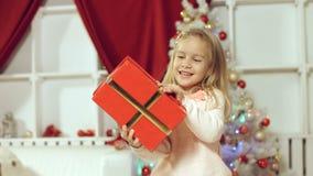 Muchacha linda que salta de la felicidad que consigue un regalo por el Año Nuevo Fotografía de archivo