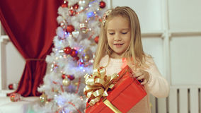 Muchacha linda que salta de la felicidad que consigue un regalo por el Año Nuevo Imagenes de archivo