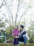 Muchacha linda que se coloca en parque con el padre Fotos de archivo libres de regalías