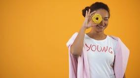 Muchacha linda que se divierte que mira a través del buñuelo, productos de la panadería, fondo amarillo metrajes