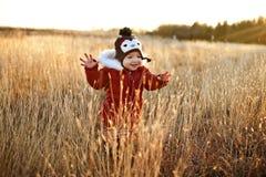 Muchacha linda que se ejecuta a través de un campo en la puesta del sol Imagen de archivo libre de regalías