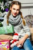 Muchacha linda que se sienta cerca del árbol de navidad en un cuarto blanco Nueva Y Foto de archivo