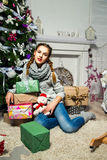 Muchacha linda que se sienta cerca del árbol de navidad en un cuarto blanco Nueva Y Foto de archivo libre de regalías