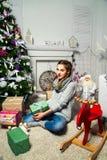 Muchacha linda que se sienta cerca del árbol de navidad en un cuarto blanco Nueva Y Imagen de archivo libre de regalías