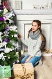 Muchacha linda que se sienta cerca del árbol de navidad en un cuarto blanco Nueva Y Fotos de archivo libres de regalías