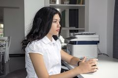 Muchacha linda que se sienta en el café, trabajo, lugar del estudio imagen de archivo