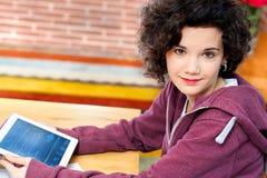Muchacha linda que se sienta en el escritorio con la tableta. Fotos de archivo