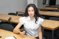 Muchacha linda que se sienta en el escritorio en sala de clase usando smartphone Foto del concepto de la educación Foto de archivo
