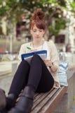 Muchacha linda que se sienta en la escritura del banco en sus notas Imagenes de archivo