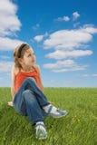 Muchacha linda que se sienta en la hierba verde Foto de archivo