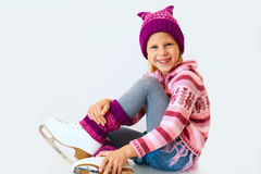 Muchacha linda que se sienta en patines de hielo Imágenes de archivo libres de regalías