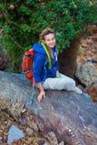 Muchacha linda que se sienta en tallo caido del árbol en bosque salvaje Foto de archivo libre de regalías