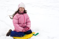 Muchacha linda que se sienta en un trineo de la nieve Fotos de archivo libres de regalías