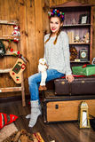 Muchacha linda que se sienta en una maleta contra el contexto del Chri Foto de archivo