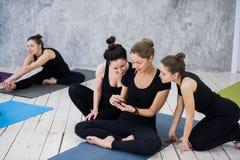Muchacha linda que se sienta y que socializa con el grupo después de su clase de la yoga imagen de archivo libre de regalías