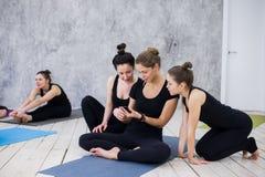 Muchacha linda que se sienta y que socializa con el grupo después de su clase de la yoga foto de archivo libre de regalías
