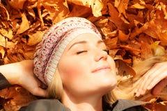 Muchacha linda que soña en las hojas de otoño Fotos de archivo libres de regalías