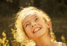 Muchacha linda que sonríe en el sol entonado Imagen de archivo