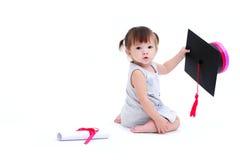 Muchacha linda que sostiene el casquillo de la graduación y el diploma del rollo Imagen de archivo