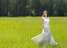 Muchacha linda que sostiene el vestido blanco en campo verde Fotos de archivo