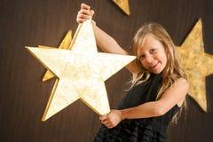 Muchacha linda que sostiene la estrella de oro grande. imagenes de archivo