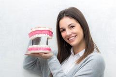 Muchacha linda que sostiene la prótesis de gran tamaño de los dientes Foto de archivo