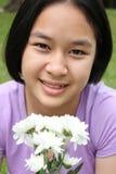 Muchacha linda que sostiene las flores blancas Fotografía de archivo libre de regalías