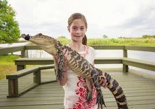 Muchacha linda que sostiene un cocodrilo cerca de los marismas de la Florida Foto de archivo