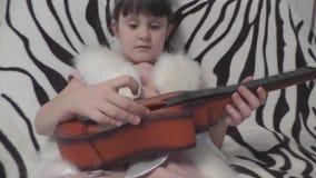 Muchacha linda que toca en el sofá la guitarra metrajes