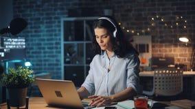 Muchacha linda que trabaja con el ordenador portátil y que disfruta de música en auricular en oficina en la noche almacen de video