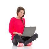 Muchacha linda que usa el ordenador portátil Imagen de archivo