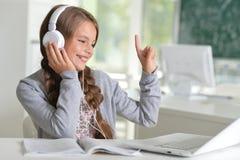 Muchacha linda que usa el ordenador portátil Imágenes de archivo libres de regalías
