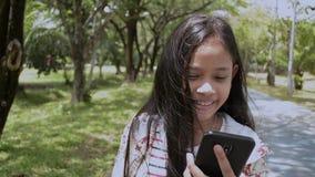 Muchacha linda que usa el teléfono móvil que camina en el parque almacen de video