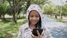 Muchacha linda que usa el tel?fono m?vil que camina en el parque almacen de metraje de vídeo