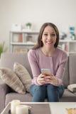 Muchacha linda que usa un smartphone Imagenes de archivo