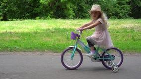 Muchacha linda sonriente que completa un ciclo en el parque Tiro del movimiento del paralelo del cardán metrajes