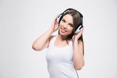 Muchacha linda sonriente que escucha la música en auriculares Imagen de archivo