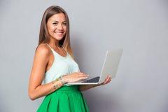 Muchacha linda sonriente que usa el ordenador portátil Fotos de archivo libres de regalías
