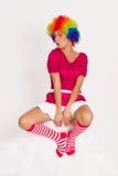 Muchacha linda vestida en peluca del payaso Imagen de archivo libre de regalías