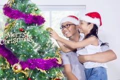 Muchacha linda y su padre que adornan el árbol de navidad Imágenes de archivo libres de regalías