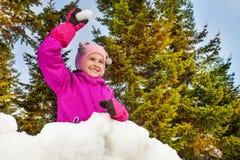 Muchacha lista para lanzar la bola de nieve en bosque Imagen de archivo libre de regalías