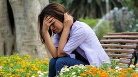 Muchacha llorosa de la minoría que se sienta en parque Foto de archivo libre de regalías