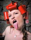 Muchacha loca de los rodillos que pega hacia fuera la cara divertida de la lengüeta Imagen de archivo